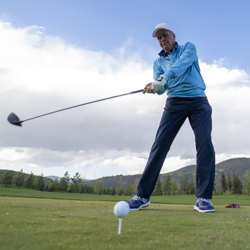 Golfer swinging with lower back tightness