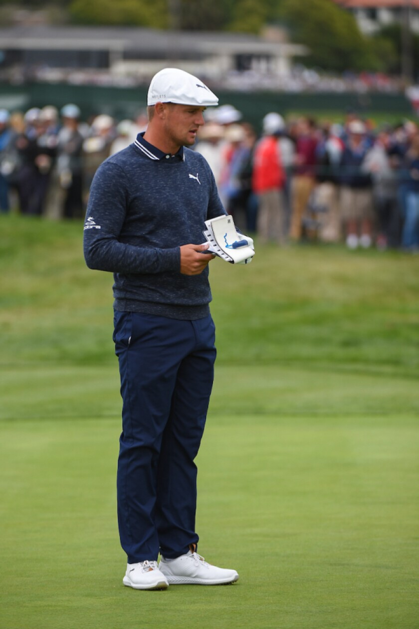 Bryson DeChambeau consulting his green book