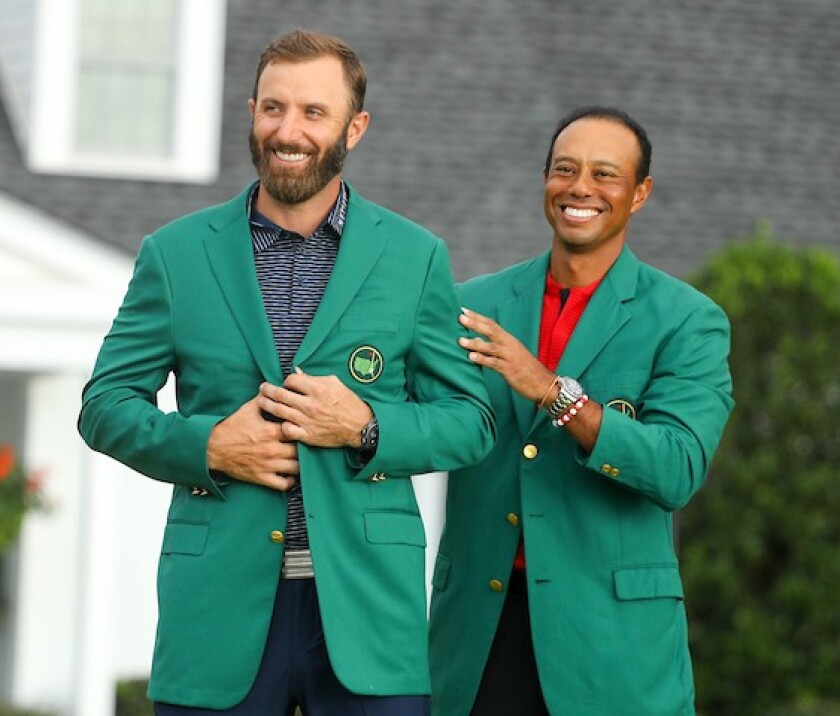 Dustin Johnson slips into the green jacket as 2020 Masters champion, with an assist from Tiger Woods